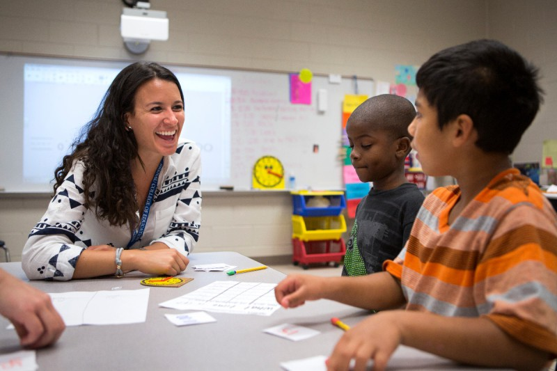 Ana Lopera works with students in the RISE program as they review how to tell time on a clock.