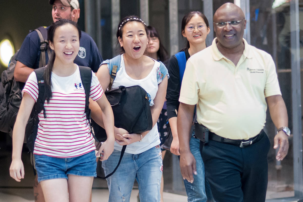 From left, Crystal Wang, Cathy Wu, Daisy Qiu and College of Education Dean Eugene Williams walk into the arrivals area at Hartsfield-Jackson International Airport in Atlanta.