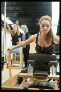 Jolie Long guides Brittany Daniel, back, as Emily Lemons works on a piece of Pilates equipment.