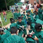 Children from the RISE program run back to their seats after throwing their hats during the RISE graduation at the Davis Street Community Center, 850 Davis Street, in Gainesville.