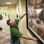 Brenau University carpenter Brian McAvoy adjusts a historic photo of the lobby in Yonah Hall that now hangs int he serving area of the Hopkins Dinning Hall.