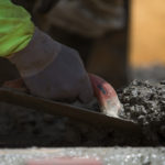 A construction workers smoothes cement for a set of stairs. (AJ Reynolds/Brenau University)
