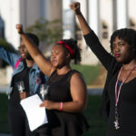 Kenya Hunter, Peyton Edmond and Diamond Wood raise their hands in the air during the Vigil for Lives Lost. (AJ Reynolds/Brenau University)