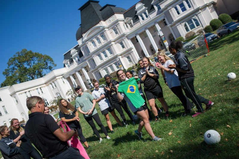 Casey Qua, a sophomore biology major, celebrates winning a t-shirt with the Brazilian flag during a soccer demonstration on Brenau's front lawn.