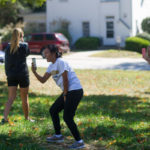Shelby Restificar, a junior biology major, center, and Sara Heard, a junior health science major, film and laugh while a friend takes a spill while attempting to complete a soccer challenge.