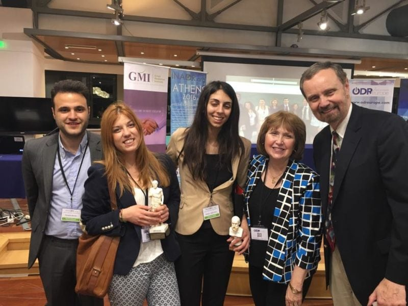 Posed photo with three Greek mediation students, left and two professors, right.