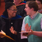 Crystal Toombs, associate provost for adult & graduate studies, laughs with Kyle Leineweber while the Brenau gospel choir performs during the Martin Luther King Jr. Day Convocation.