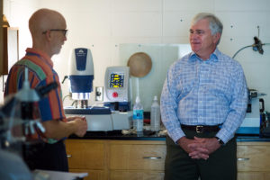 Bill Miller, professor emeritus in the geology department at the University of North Carolina Asheville, talks with Brenau President Ed Schrader during the filming of Return to Roanoke: Search for the Seven, a History Channel program, at the University of North Carolina Asheville. Brenau President Ed Schrader took the Dare Stone to undergo scientific testing in order to learn more about its origin. (AJ Reynolds/Brenau University)