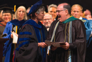 Provost and Vice President for Academic Affairs Nancy Krippel presents Perry Daughtry, assistant professor of psychology, with the Vulcan Teaching Award during the spring commencement ceremony for the Women's College at Brenau University. (AJ Reynolds/Brenau University)