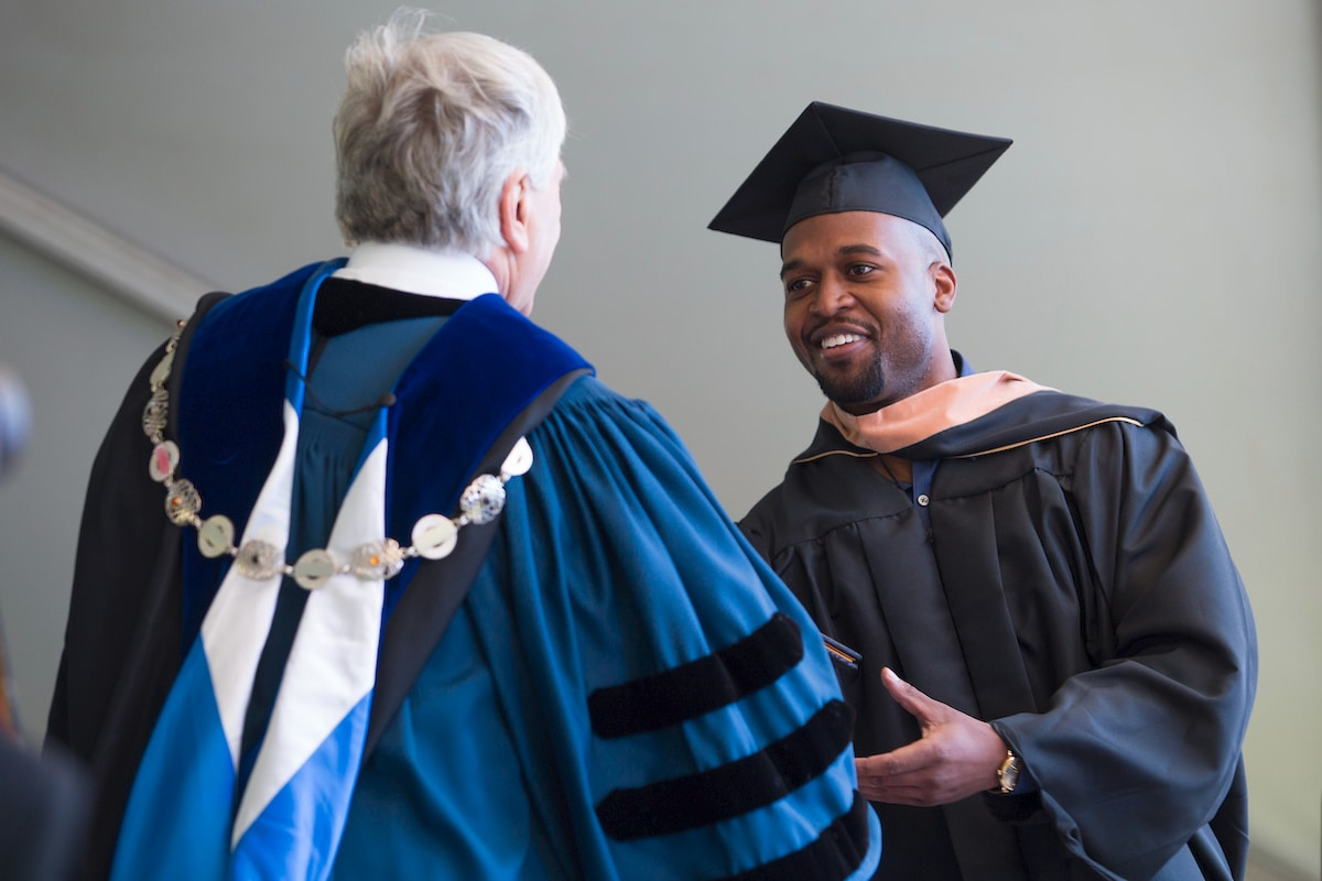 Kristopher Lamar Skyes receives his Master of Business Administration degree from Brenau President Ed Schrader during the Brenau University Graduate and Undergraduate Commencement ceremony. (AJ Reynolds/Brenau University)