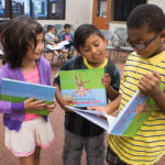 "Ailyn Marquez, from left to right, Brandon Perez and Kendrick Parker look at their books during the presentation of ""Lucile Shows Kindness,"" the sixth edition of Tiger Tales. This year's book was produced in a partnership between Brenau and Ana Hortman's second grade class at Fair Street Elementary. (AJ Reynolds/Brenau University)"