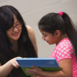 "Lavender Qin, an early childhood education major from Wuhu, China, talks with Angie Chavez during the presentation of ""Lucile Shows Kindness,"" the sixth edition of Tiger Tales. This year's book was produced in a partnership between Brenau and Ana Hortman's second grade class at Fair Street Elementary. (AJ Reynolds/Brenau University)"
