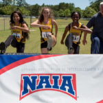 From left to right Cheyenne Wells, a senior from Sandy Springs, Ga., Sydney Romine, a freshman from Jasper, Ga., Ismaelle Occeus, a senior from Lawrenceville, Ga., and Brenau head coach Byron Kramer pretend to hurdle an NAIA banner while posing for a photo during the NAIA Track & Field Championships in Gulf Shores, Ala. (AJ Reynolds/Brenau University)