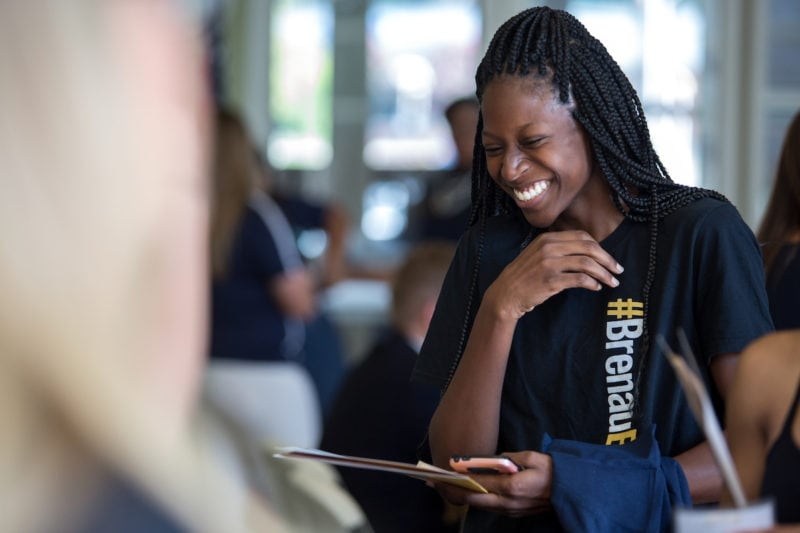 Nardaiser Harris laughs while receiving her orientation t-shirt at check in. (AJ Reynolds/Brenau University)