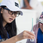 Michael Zihan Shao, left, and Yolanda Xuan Guan examine samples while testing the water quality in Lake Lanier with their science concepts class. (AJ Reynolds/Brenau University)