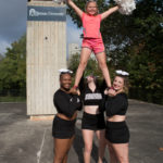 Brenau cheerleaders lift a girl into a stunt during a National Fitness Day event at Brenau. Brenau student-athletes spent time with children from the Boys & Girls Club of Lanier practicing various athletic activities. (AJ Reynolds/Brenau University)