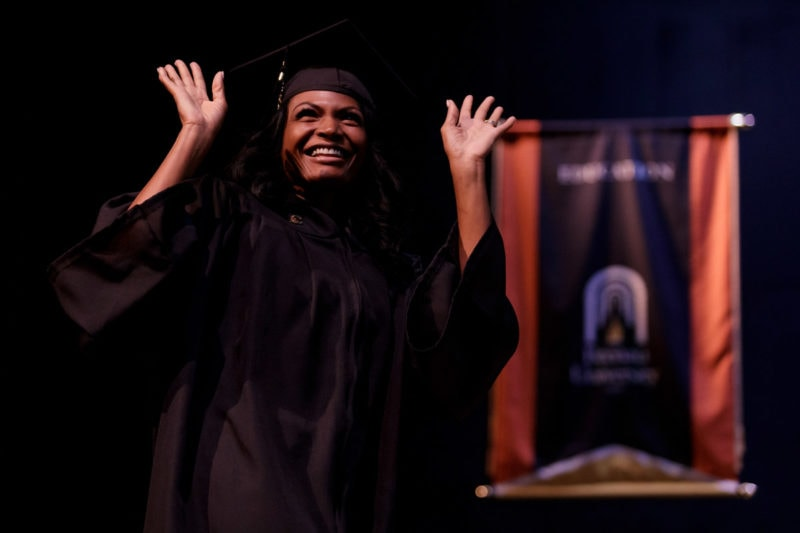 Tangela Darnise Hendricks waves while walking across the Pearce Auditorium stage during the Brenau University undergraduate and Women's College winter commencement ceremony. (AJ Reynolds/Brenau University)