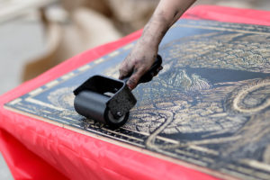 A large printing block is inked using a roller.