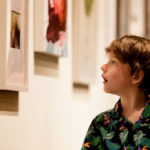 A young boy takes in some of the art on display during the President's Summer Art Series reception.