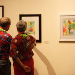 Two attendees study some of the artwork of Lyndrid Patterson while making their way through the exhibition.