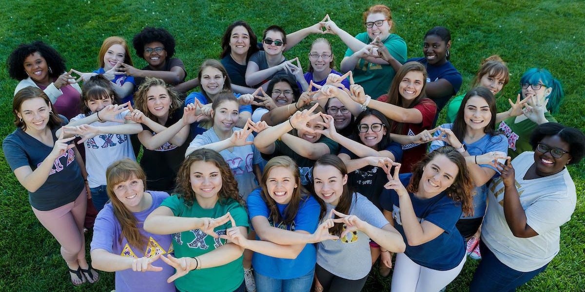 Representatives from Brenau's eight sororities make delta signs together with their hands