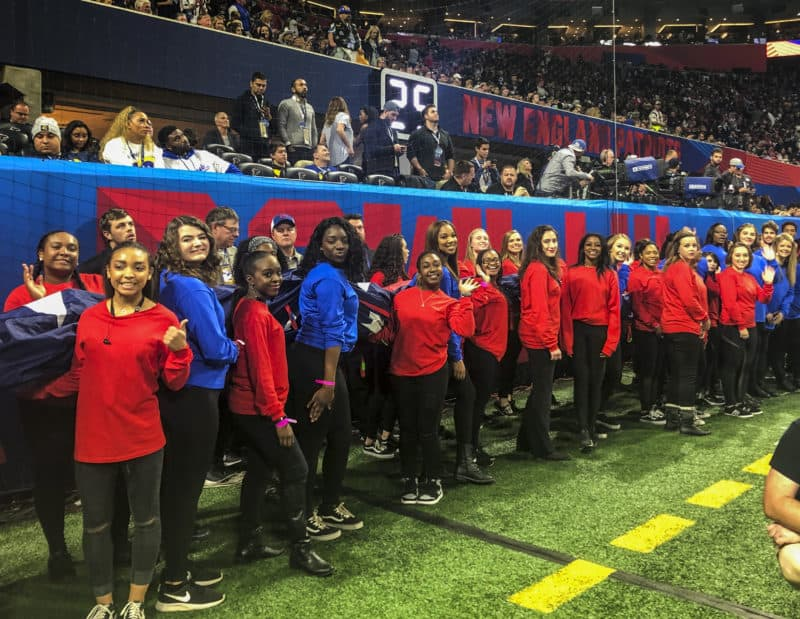 Brenau University student-athletes from the competitive cheer and dance teams line up with the American flag before the pregame festivities at Super Bowl LIII on Sunday, Feb. 3, in Mercedes-Benz Stadium.