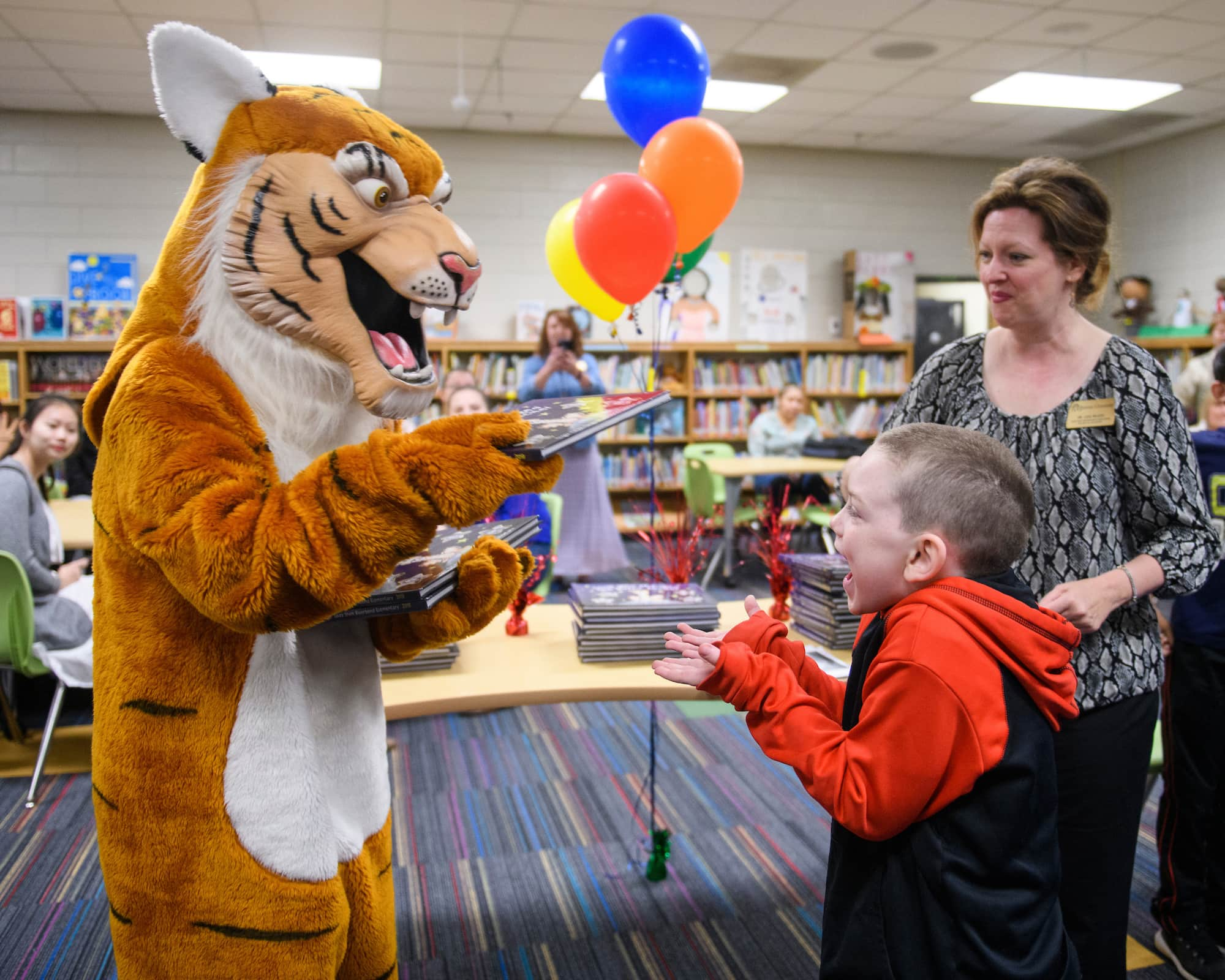 Student receives book from tiger mascot.
