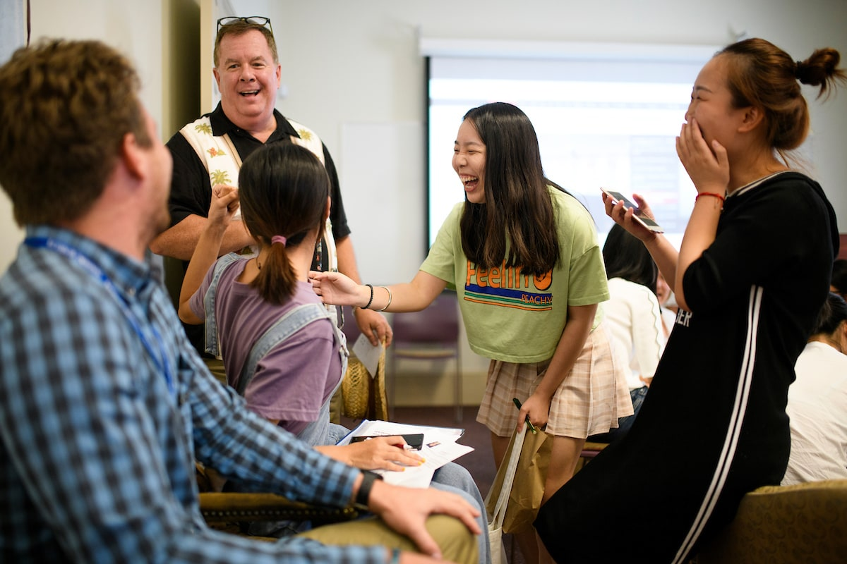 Brenau faculty and students from China laugh while work on a project