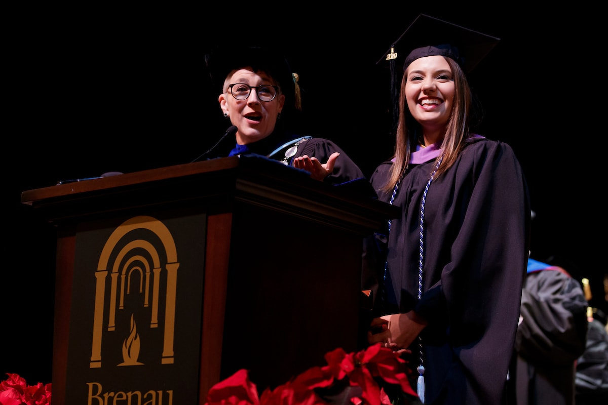Anne Skleder and Jenna Schardt at Brenau podium during winter commencement.
