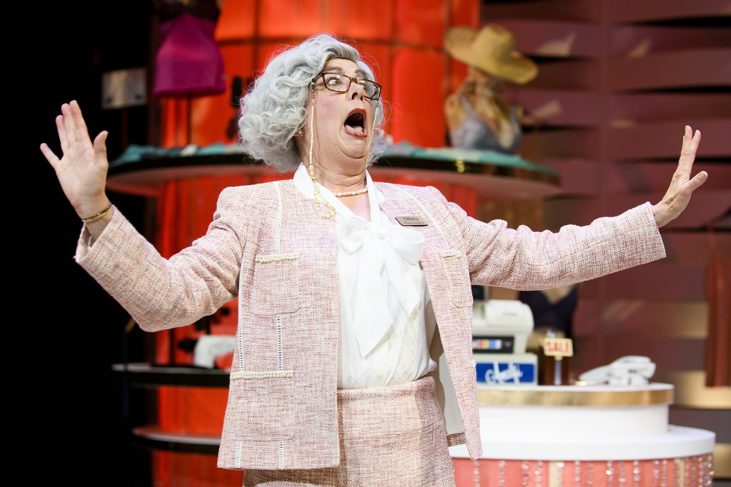 An actress playing a sales woman yells comedically in a play