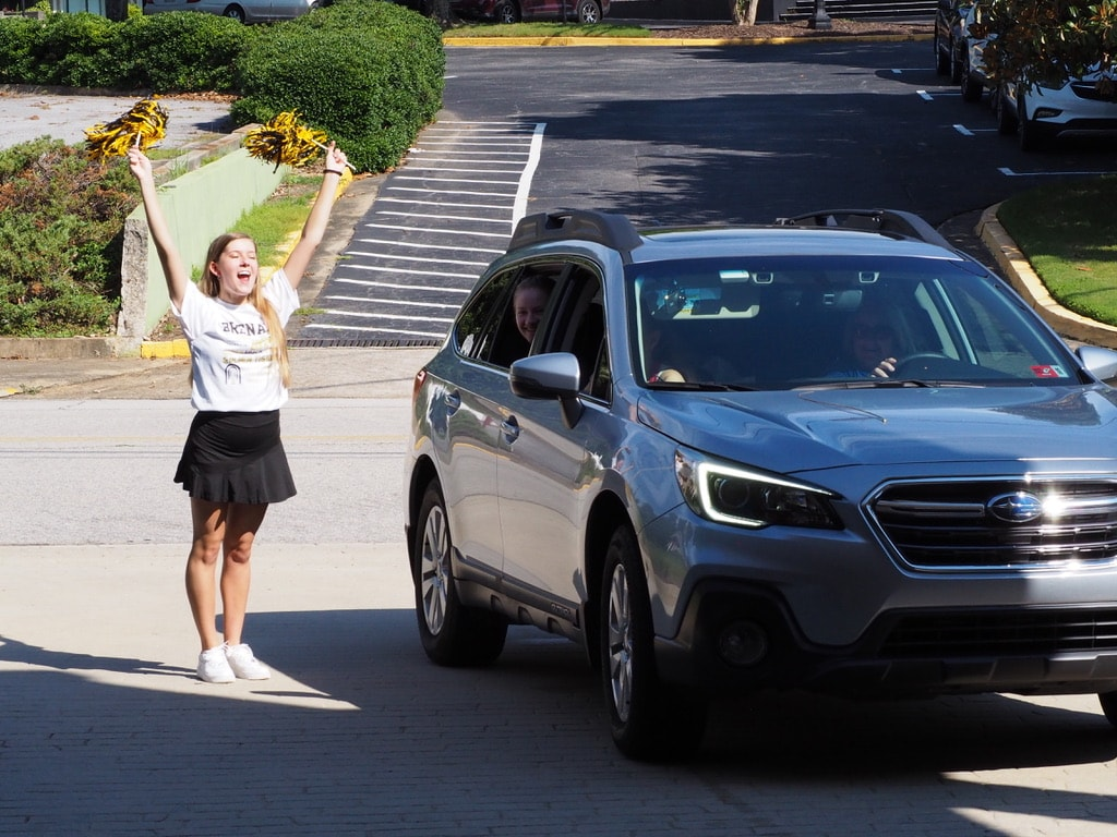 Tiffany Oltjenbruns, junior dance major, cheers as students check-in